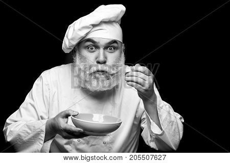 Bearded man cook in hat tasting food with spoon in studio on black background