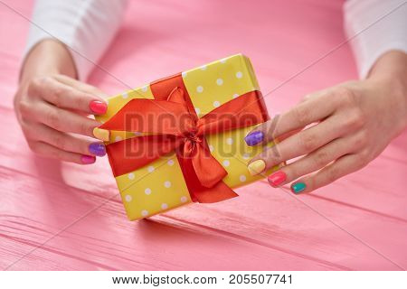 Female hands and yellow gift box. Female beautiful hands holding gift box close up, wooden background.