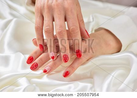 Female red and dotted manicure. Womans beautiful manicured hands with a pattern of hearts on white silk.
