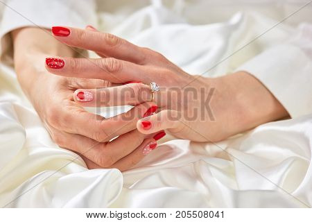 Woman hand touching her ring on finger. Well-groomed female hands with engagement ring. Female manicured hand with beautiful ring.