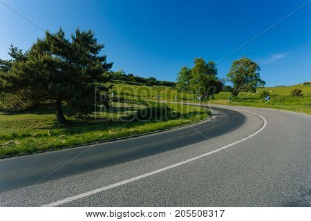 Empty Asphalt Curvy Road Passing Through Green Fields And Forests. Countryside Landscape On A Bright