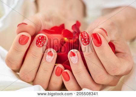 Red romantic manicure and petals. Beautiful hands with perfect red patterned manicure on treated nails holding rose flower petals. Romance conceptual image.
