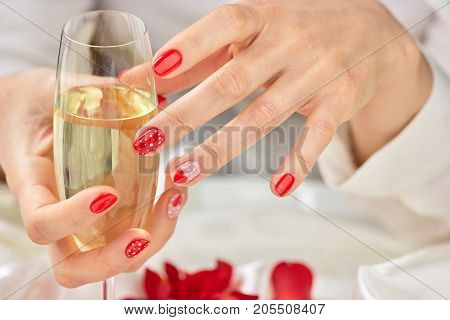 Female manicured hands with champagne. Woman hands with beautiful romantic design manicure holding glass of champagne.