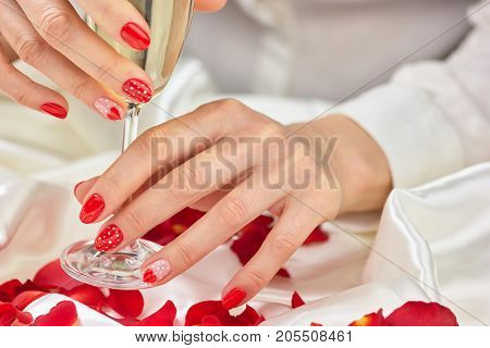 Beautiful female hands with champagne. Young lady hands with romantic manicure holding glass of champagne close up.