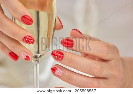 Glass of champagne in manicured female hands. Lady hands with beautiful winter manicure holding glass of champagne.