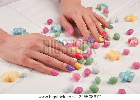Girls manicured hands and sweets. Girls hands polished with different colors and colorful candies on white wooden background.