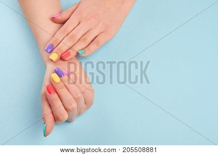 Hands with short manicured nails. Manicure covered with nail polish in summer colors. Girls manicured hands and copy space.