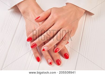 Female well-groomed manicured hands. Woman beautiful hands with red hearts and dots design manicure on white wooden table. Skin and nail treatment.