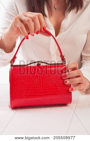 Female hands holding red handbbag. Woman with beautiful manicure holding bright lacquered clutch on white wooden table.