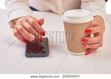 Woman with coffee using smartphone. Female manicured hands holding disposable cup of coffee and using touch screen phone, white wooden table.