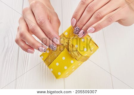 Yellow gift box in female hands. Little gift box with golden ribbon in female hands with beautiful manicure. Holidays and celebrations concept.