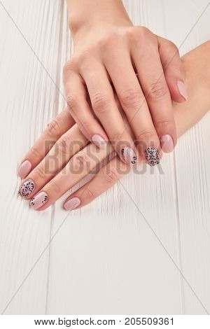 Nice manicured woman fingernails. gentle polished nails in beige color with patterns. Skin and nails treatment.