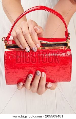 Red lacquered bag in female hands. Female manicured hands holding red leather handbag. Womans fashion and style, topview.