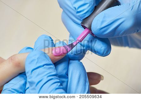 Beautician painting nails to client. Manicurist applying pink varnish on female nails. Nails beauty salon.