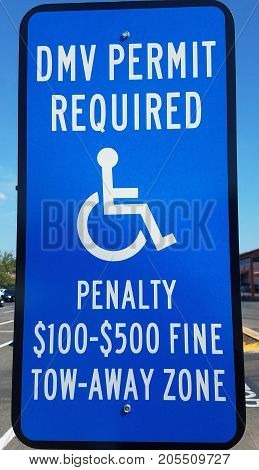 a blue DMV permit required sign with wheelchair and penalty information