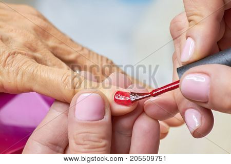 Manicurist applying red varnish to senior woman. Nails beautician painting nails to old woman in beauty salon.