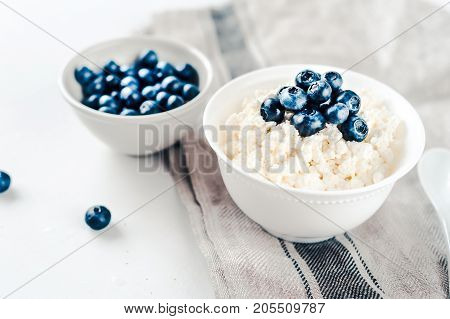 Fresh cottage cheese with blueberries on wood white