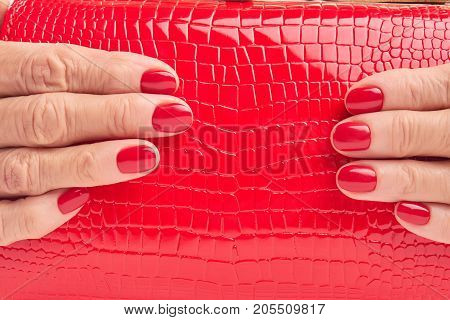 Close up red leather purse in female hands. Woman hands with red manicure holding red lacquered handbag close up.