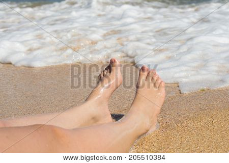 Two legs lie on a beach on a wave background
