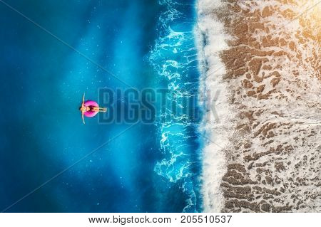 Aerial view of young woman swimming on the pink swim ring in the transparent turquoise sea in OludenizTurkey. Summer seascape with girl beautiful waves azure water in sunny day. Top view from drone