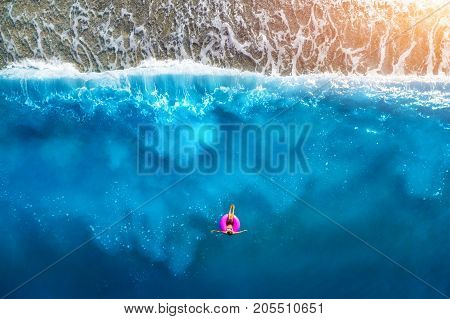 Aerial view of slim woman swimming on the pink swim ring in the transparent turquoise sea in OludenizTurkey. Summer seascape with girl beautiful waves blue water in sunny day. Top view from drone