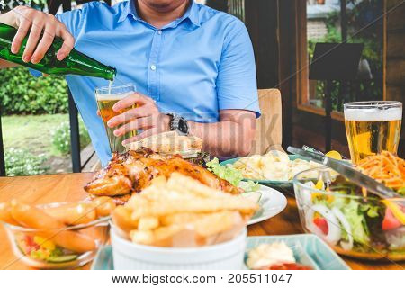 Young asian man drinking beer and eatting foods happy while enjoying home