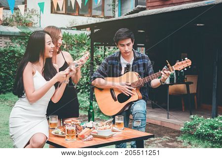 Group Of Young Asian People Happy While Enjoying Home Party And Play Guitar On Garden Home