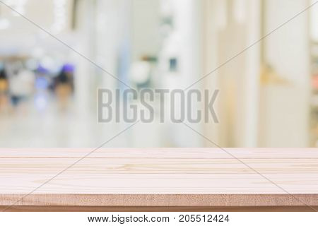 Wood table top on blurred with bokeh shopping mall background - can be used for display or montage your products.