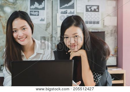 Beautiful young Asian girl and businesswoman meeting & explaining at a home office with a laptop. Concept of female leader working.Vintage tone