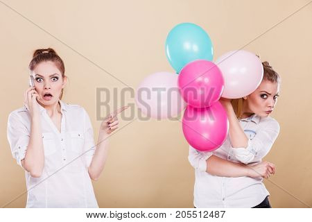 Two girls with colorful balloons and mobile phone. Best friends preparing party celebration having problem bad relationship