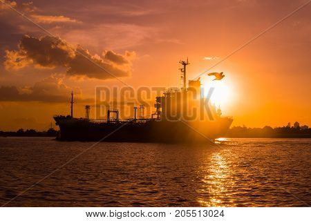 Logistics and transportation of International Container Cargo ship in the ocean at sunsetand silhouette of boat
