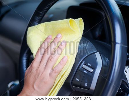 Hand cleaning interior car steering wheel with microfiber cloth