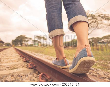 Retro style of woman walking on the railway. Travel and step concept.