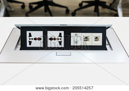 Electrical outlet with dual 3 pin phone jack plugs and Network plugs on a white table background