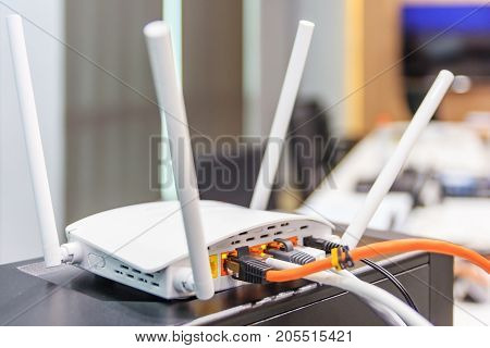 Closeup of Wi-Fi wireless router with cables and wan port in conference room communication technology background