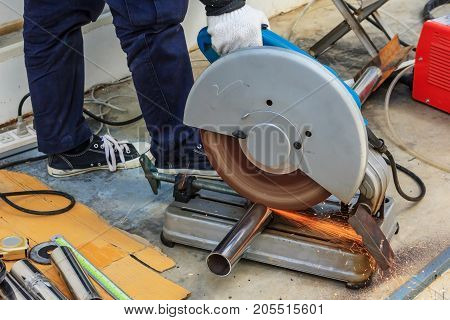 Industrial worker cutting metal with many sharp sparks working on compound mitre saw with circular blade