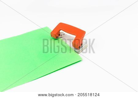 An Orange Paper Punch With Green Paper Isolated