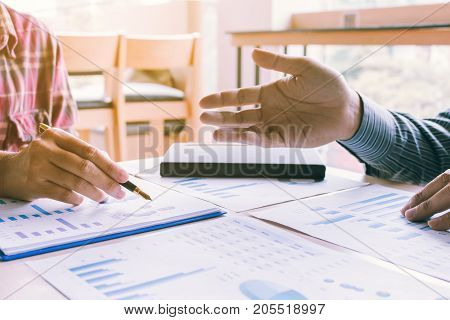 Coaching And Advising With Two Business Man Working Together And Talking And Analyzing About Financi