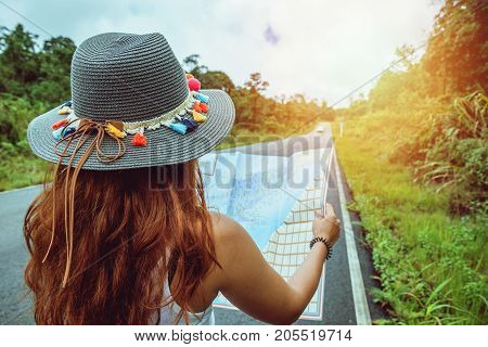 Asian women travel relax in the holiday. Take a look at the map on a rural road in the middle of nature. Thailand