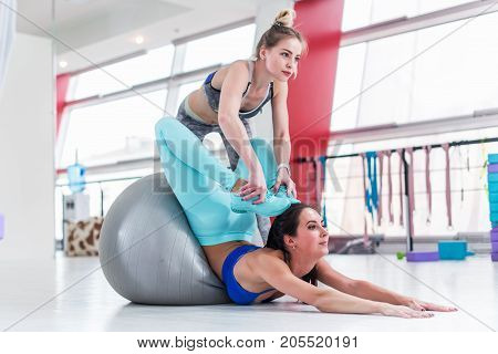 Flexible woman doing advanced stretching exercise. Pretty female instructor helping slim brunette girl do yoga Locust pose with feet touching head in gym.