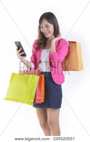 Shopping young asian women holding mobile phone and shopping bags on white studio background.(Sale and shopping online concept)