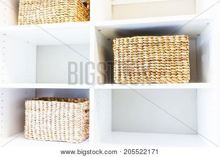 Closeup Of Woven Straw Baskets In Modern Minimalist White Closet Or Laundry Room With Bright Light I