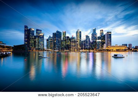 Beautiful illuminated Singapore central business district skyline at dusk under blue hour night sky Singapore Asia. Long time exposure