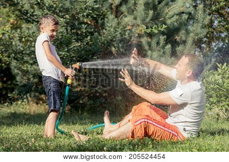 Happy Father And Son Playing In The Garden At The Day Time.