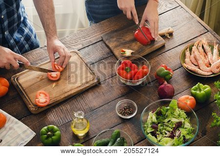 Top view couple cooking together delicious and healthy dinner on a wooden table in home kitchen