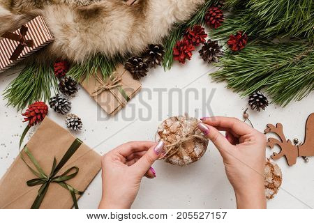 Preparing festive presents for Christmas and New Year. Sweet cakes binding by unrecognizable woman near decoration from pine and wrapped gifts, top view. Congratulation and homemade decor concept