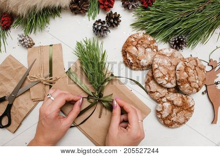 Preparing festive presents for Christmas and New Year. Top view gifts wrapping by unrecognizable woman on table, decoration from pine and sweet cakes nearby. Congratulation and homemade decor concept