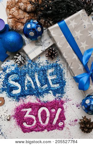 Sales on Christmas and New Year holidays, top view reversed. Festive decoration with informative inscription of 30 pct discount for shop-windows, shopping malls and advertizing background concept