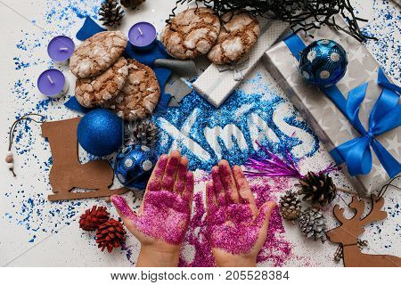 Christmas festive background top view. Kid hands in glitter on wrapped presents, different handmade decoration and bright xmas inscription backdrop. Holiday decor and celebration concept