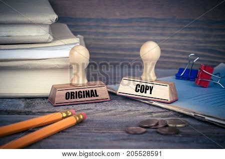 Original and Copy concept. Rubber Stamp on desk in the Office. Business and work background.